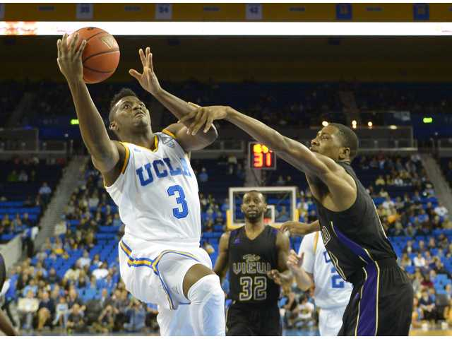 UCLA guard Jordan Adams, left, puts up a shot as Prairie View forward Hershey Robinson on Saturday in Los Angeles.