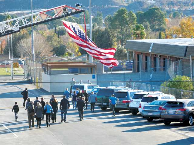 Fire station 126 displays an American flag on the ladder of their truck as attendees head for the memorial service of Santa Clarita Valley Sheriff's Deputy Devin Freeman, held in the Canyon High School gymnasium in Canyon Country on Saturday.