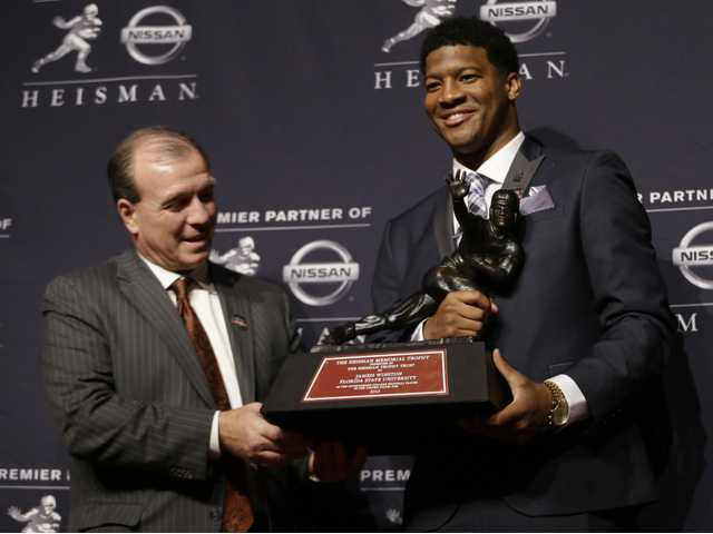 Florida State quarterback Jameis Winston, right, stands with FSU coach Jimbo Fisher while holding the Heisman Trophy.