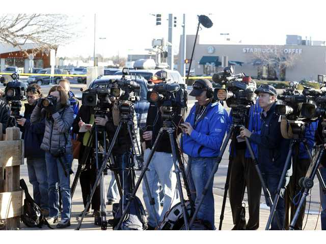 Media cover a briefing by Arapahoe County Sheriff Grayson Robinson on Saturday at Arapahoe High School in Centennial, Colo.
