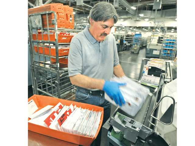 Castaic resident and mailroom clerk  Richard Preble loads letters into the bar code reader on the floor of the Santa Clarita Processing and Distribution Center in Castaic. Signal photo by Dan Watson.