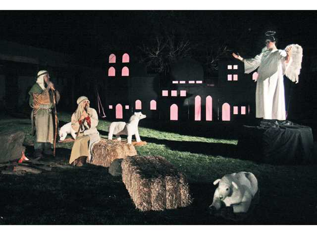 "Steve Eaton, and Melinda Gilmore, center, portray shepherds listening to an angel's message in Jerusalem, played by Harry Eaton during the ""Living Nativity"" performance on Saturday night. Photo by Natalee Ayala for The Signal."