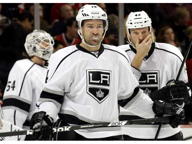 Los Angeles Kings Justin Williams (14), center, goalie Ben Scrivens, left, and Robyn Regehr enter the ice on Sunday in Chicago.