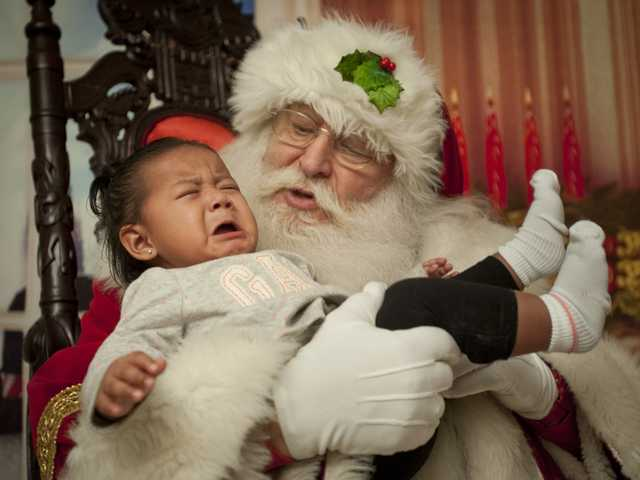 Stan Taub, dressed as Santa, consoles eight-month-old Yanet Lopez, at the Park Sierra apartment complex in Canyon Country. Signal photo by Charlie Kaijo.