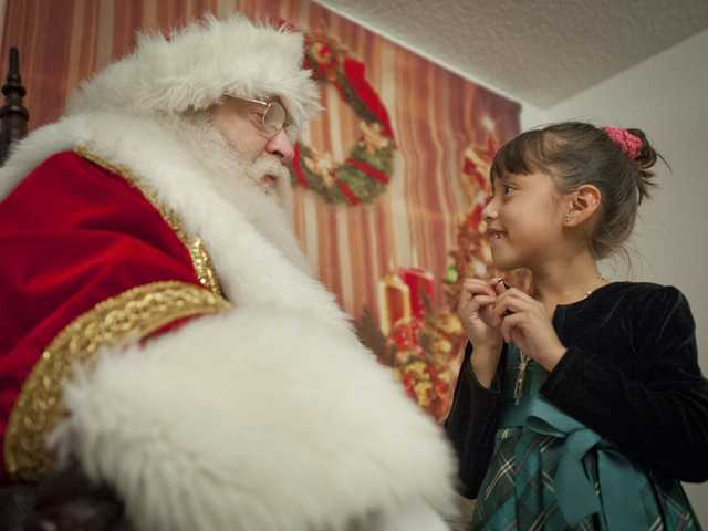 Stan Taub, dressed as Santa, greets 6-year-old Leslie Betancourt at the Park Sierra apartment complex in Canyon Country. Signal photo by Charlie Kaijo.