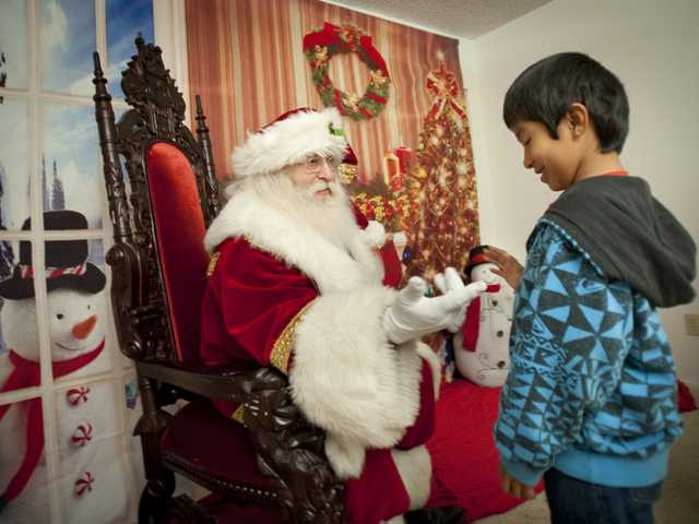 Isaiah Quintero, 8, gets greeted by Mr. Claus during the Christmas party on Monday. Signal photo by Charlie Kaijo.