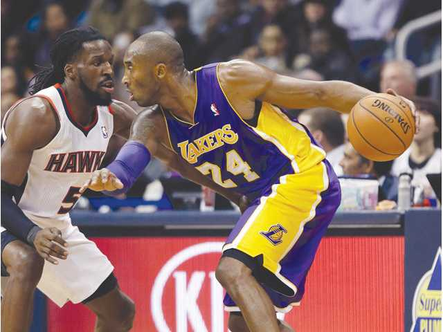 Los Angeles Lakers guard Kobe Bryant (24) works against Atlanta Hawks forward DeMarre Carroll (5) on Monday in Atlanta.