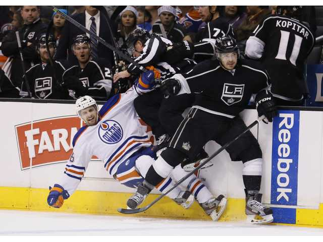 Los Angeles King Drew Doughty, right, checks Edmonton's Mark Arcobello on Tuesday night in Los Angeles.