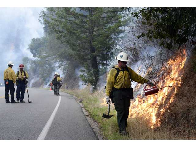 Firefighters light a backfire along Highway 1 between Pfeiffer Ridge Road and the Big Sur Station in Big Sur, Calif., on Wednesday.
