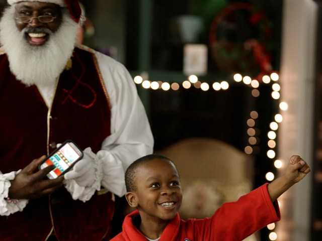 "In this Tuesday photo, Dee Sinclair, who bills himself as the ""Real Black Santa"" smiles as Paris Allen, 7, reacts after passing a naughty or nice test in Atlanta."