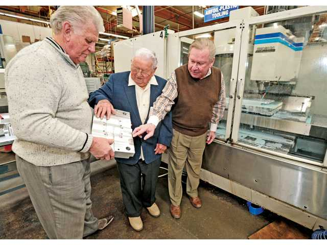 Tom Schrey, left, stands with father Walt and brother Bill as they examine a milled aluminum part created on the computerized milling machine behind them at Schrey & Sons Mold Co. Inc. in Valencia on Tuesday.