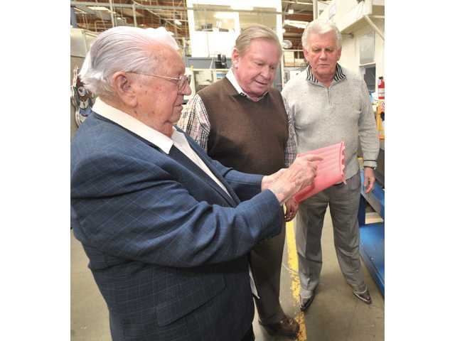 From left, Walt Schrey and his sons, Bill and Tom, examine a mold of an aircraft engine part created at Schrey & Sons Mold Co. Inc. in Valencia on Tuesday.