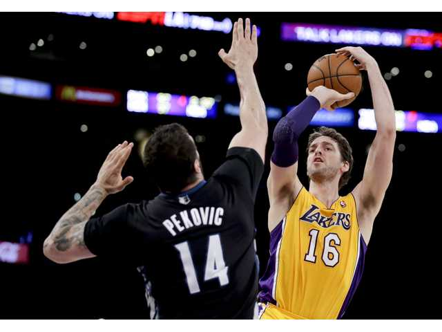 Los Angeles Lakers center Pau Gasol shoots over Minnesota Timberwolves center Nikola Pekovic on Friday in Los Angeles.