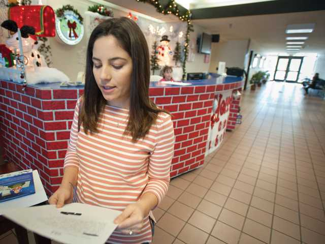 Pela McHenry from Granada Hills reads a child's Christmas letter written to Santa at the Santa Clarita Processing and Distribution Center in Castaic. Operation Santa allows people to answer letters and donate gifts to children who write letters to Santa.