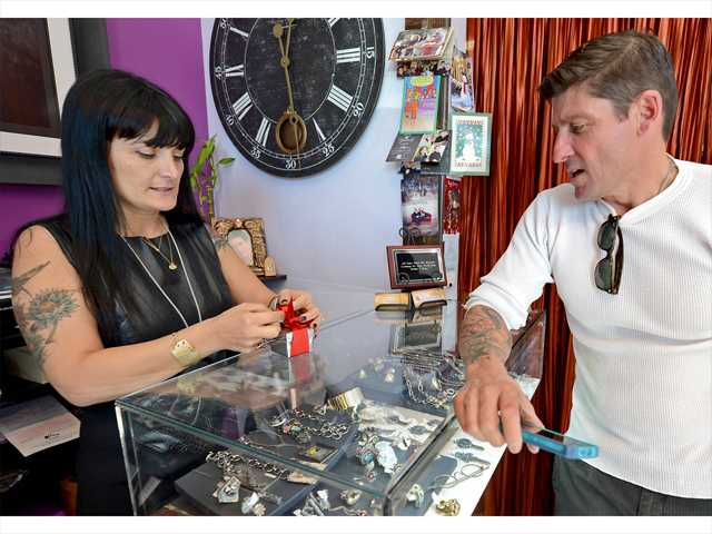 LuisMarquez makes a purchase of handmade silver ring with black diamonds at Manya Jewelers for his wife as owner Manya Nazarian wraps the gift Sunday at the Valencia Town Center. Photo by Jayne Kamin-Oncea for The Signal.