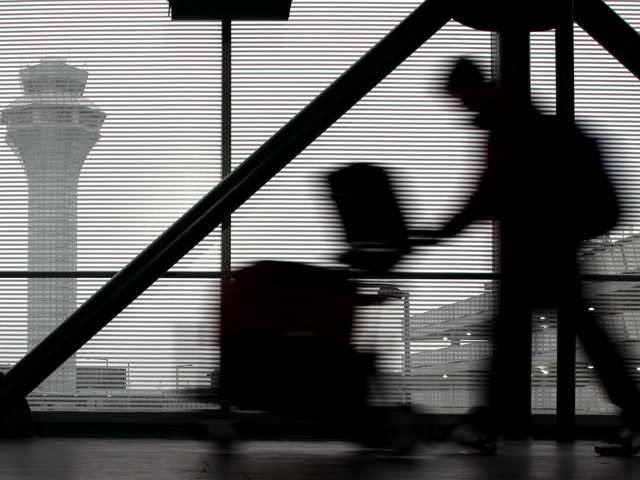 A traveler walks through Terminal 3 at O'Hare International Airport in Chicago on Saturday, Dec. 21, 2013. The National Weather Service issued a hazardous weather outlook for north central Illinois, northeast Illinois and northwest Indiana Saturday morning.