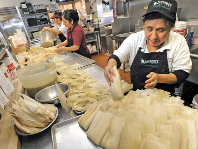 From left, Maria Garbay and Margarita Pena add sauce and chicken to tamales as Balvina Ortiz, right, folds corn husks around them and places finished tamales on a pan for steaming at Jazmin's Bakery. Jazmin's orders for tamales triple in December. Signal photo by Dan Watson