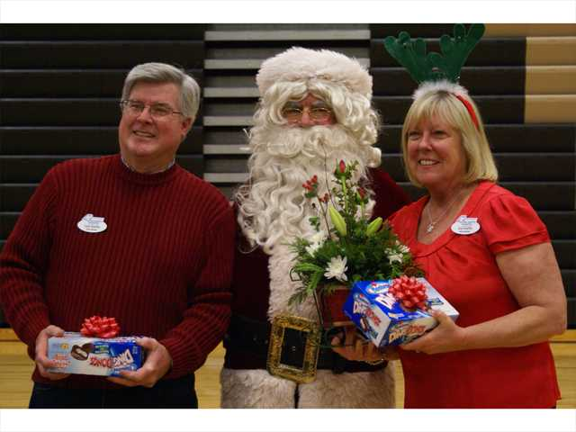 Chris and Sue Hoefflin, the parents of Michael Hoefflin for the which the foundation was named, pose with Santa Sunday at the annual Michael Hoefflin Foundation & Golden Valley High School Holiday Party for Kids with Cancer. Signal photo by Jim Holt.