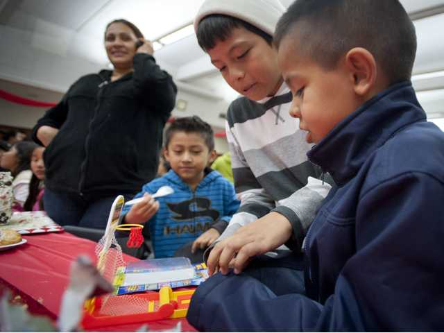 Sergio Emiliano, 7, and his cousins play with a basketball toy he received as a gift from Santa at the Hart High School Cafeteria for the 21st anniversary dinner serving Santa Clarita communities in need. Signal photo by Charlie Kaijo.