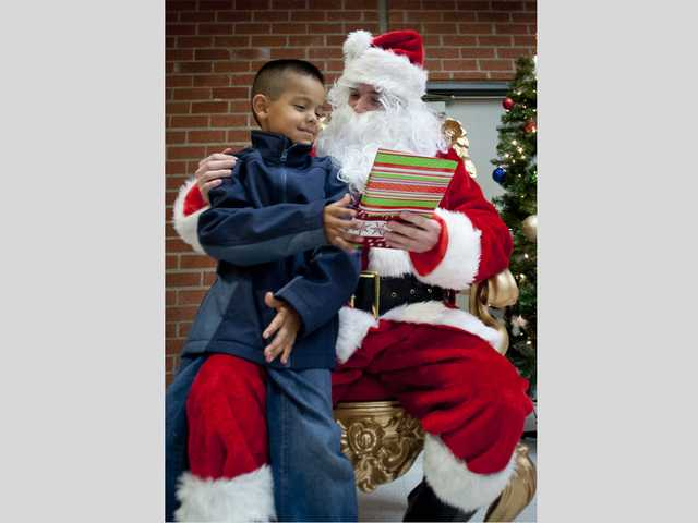 Hart High School ASB president, Drew Turner dressed as Santa, gives a gift to 7-year-old Sergio Emiliano at the cafeteria of Hart High School. Signal photo by Charlie Kaijo.