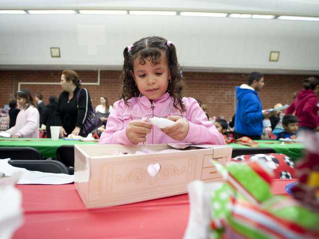Kimberly Sandoval, 4, plays with a toy given to her by Santa in the Hart High School cafeteria at the 21st annual holiday dinner. Signal photo by Charlie Kaijo.