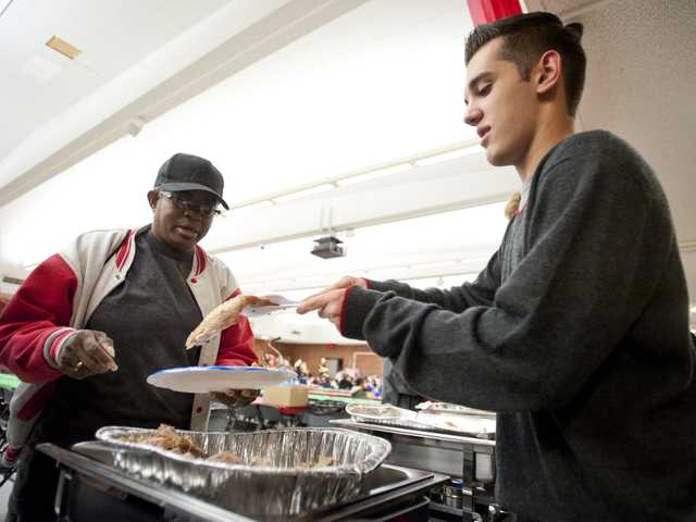 "Hart High School ASB member Rocky Novaes, right, serves turkey to Vivian Pheifer at the school's 21st annual ""Feed the Needy"" dinner Friday night at the school cafeteria. Signal photo by Charlie Kaijo"