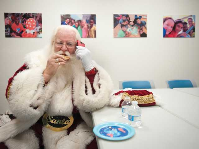 Stan Taub, dressed as Santa Claus, talks on the phone while eating cookies before making an appearance at the Newhall Community Center for a holiday event. Signal photo by Charlie Kaijo.