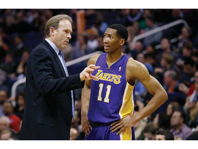 Los Angeles Lakers assistant coach Kurt Rambis, left, talks with Wesley Johnson (11) on Monday in Phoenix.