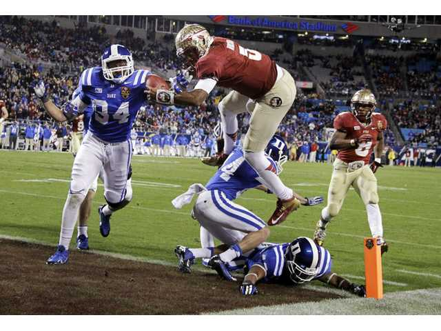 In this Dec. 7 file photo, Florida State's Jameis Winston (5) leaps over Duke's Bryon Fields (14) for a touchdown in Charlotte, N.C.