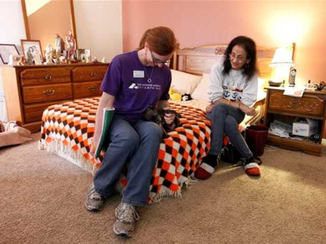 In this Dec. 15, 2013 photo, Mary Birrell, left, volunteer, pets Kane, a 6-year-old Chihuahua, while dropping off dog food to Kane's owner, Gloria Hernandez-Rosado, right, in Tampa, Fla.