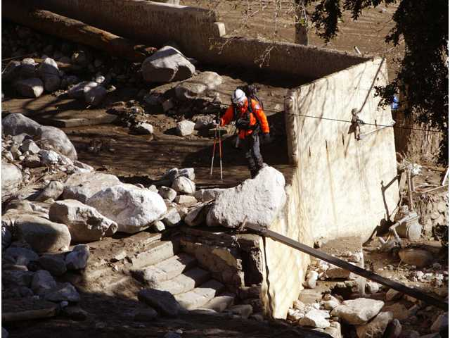 In this Dec. 27, 2003, file photo, a rescue worker searches for victims after devastating mudslides swept through the Waterman Canyon area of the San Bernardino.