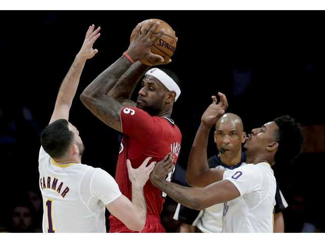 Miami Heat forward LeBron James, middle, is double-teamed by Los Angeles Lakers in Los Angeles on Wednesday.