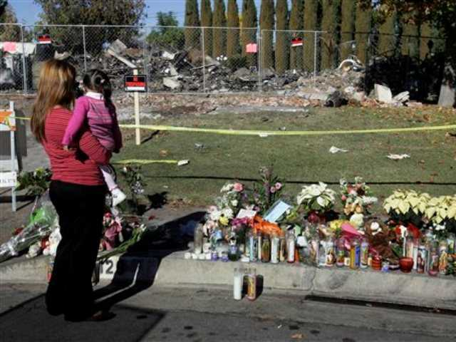 In this Dec. 29, 2008 file photo, a woman and a girl visit a memorial set up near the ruins of the Ortega family home in Covina, Calif. Bruce Pardo, dressed as Santa, shot indiscriminately at partygoers and destroyed his former in-laws' house with a homemade blowtorch, ultimately leaving nine people dead before killing himself.