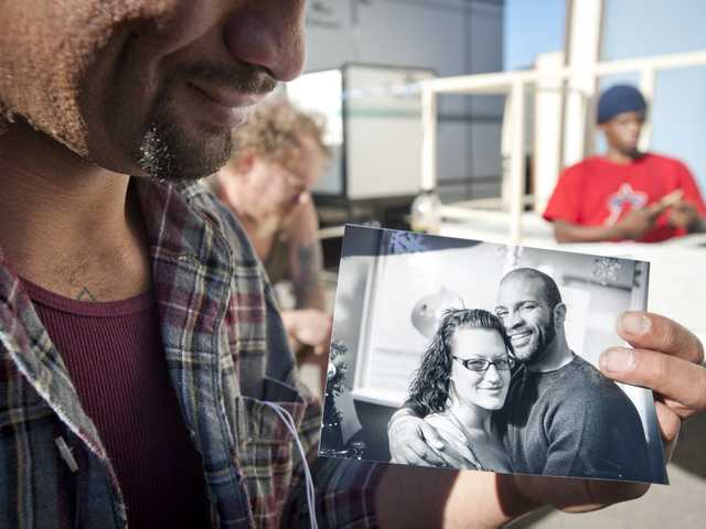 Bryan Woodson shows a Christmas portrait of him and his fiance Heather at the Bridge to Home homeless shelter in Newhall on Wednesday.