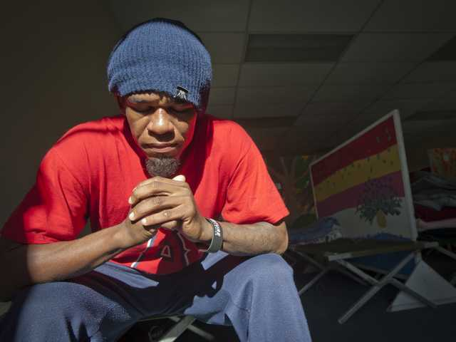 Cartlon Searcy-Cooper sits for a portrait in the bunking area of the Bridge to Home homeless shelter.