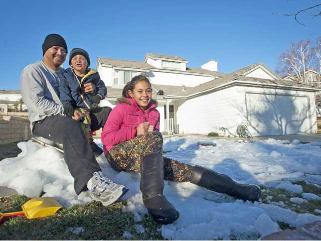 Kris Samana, left, and his two kids, Elijah and Alana Greene, sit in the snow on their lawn early Wednesday morning.