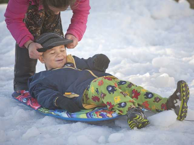 Alana Greene, left, puts a hat on her little brother, Elijah Greene, while playing on the plot of snow placed on the lawn of their home in Canyon Country on Wednesday.