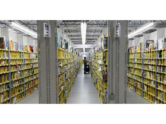 In this Dec. 2 file photo, an Amazon.com employee stocks a shelf at an Amazon.com Fulfillment Center.