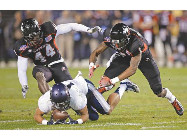 Utah State receiver Shaan Johnson beats Northern Illinois defenders on Thursday in San Diego.