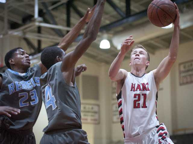 Hart's Luke Maly throws a layup past two South Bakersfield defenders during Thursday night's game at Hart High.
