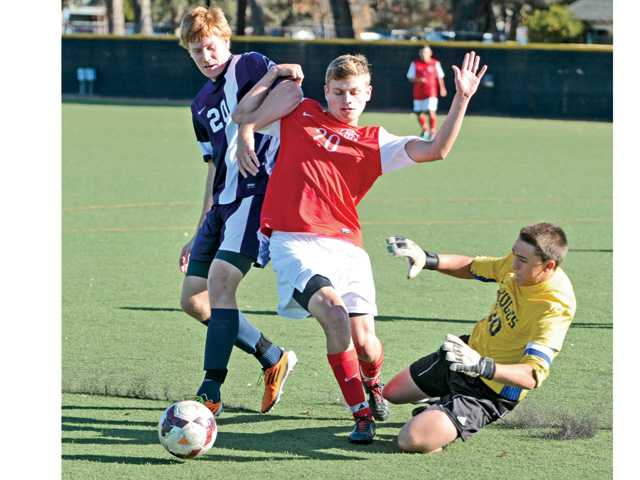 Hart's Andrew Nielsen, centerm takes a shot that is defended by Saugus' Colin Maher, left, on Friday at Reese Field.