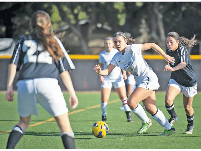 Valencia's Carolina Velez dribbles down field past a Knight High defender on Friday at The Master's College's Reese Field.