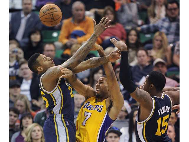 Utah Jazz's Brandon Rush, left, and Derrick Favors defend Los Angeles Lakers' Xavier Henry (7) on Friday in Salt Lake City.