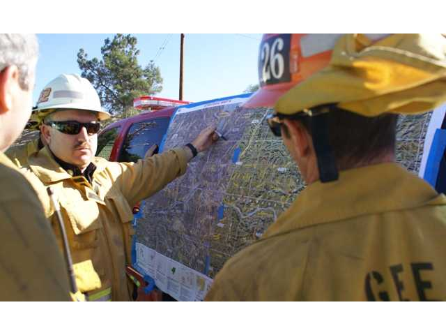Battalion Chief Tom Stukey of the Los Angeles County Fire Department discusses containment strategies with firefighters during a Sunday morning brush fire off of San Francisquito Canyon Road in Saugus. Signal photo by Jim Holt