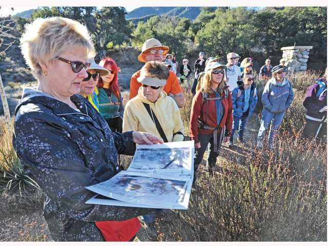 Ruth Anne Murthy, left, looks at photos of the 1909 Walker family homestead as she and a group of hikers stand near the remains of the original Walker house in the Golden Valley Ranch Open Space area on Saturday. Signal photo by Dan Watson.