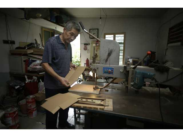 "In this Sept. 9 photo, Dong Linhua, 59, works at his workshop in Shanghai. ""I heard that the authorities might postpone the age of the retirement, but I sure hope not, since I've already worked for almost 42 years,"" says Dong."