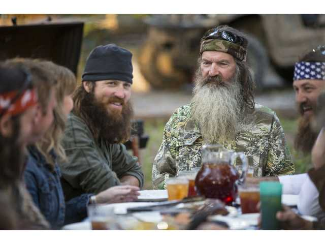 "This undated image released by A&E shows Phil Robertson, flanked by his sons Jase Robertson, left, and Willie Robertson from the popular series ""Duck Dynasty."""