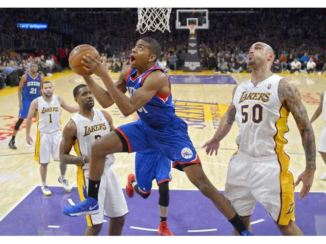 Philadelphia 76ers forward Hollis Thompson, center, puts up a shot against Lakers defenders on Sunday in Los Angeles.