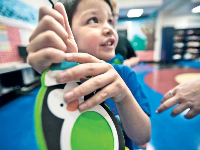 Five-year-old Ethan Venturo holds up a Christmas ornament he made during a day at the center. Signal photo by Charlie Kaijo.