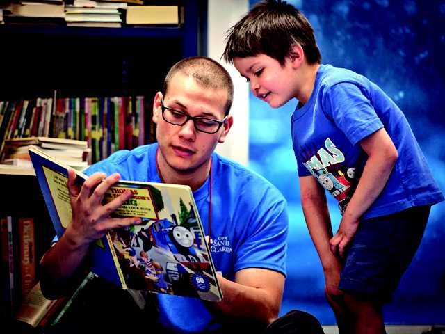 Counselor Mac Saldana reads to five-year-old Ethan Venturo at the Newhall Community Center on Monday. Signal photo by Charlie Kaijo.